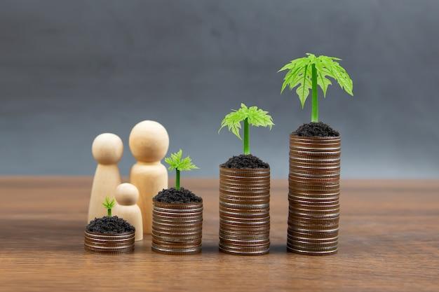 Las monedas se apilan en forma de gráfico con el símbolo familiar y el árbol joven de un árbol en crecimiento