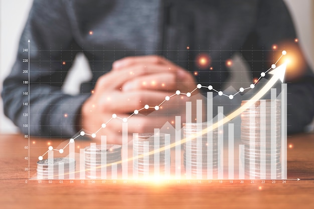 Las monedas se apilan con un gráfico virtual y aumentan la flecha frente al empresario. inversión empresarial y concepto de ahorro de ganancias.