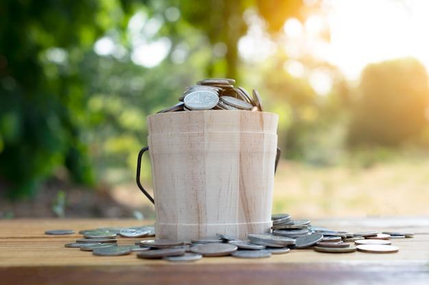 Monedas de baht tailandés en caja de madera sobre fondo verde de mesa
