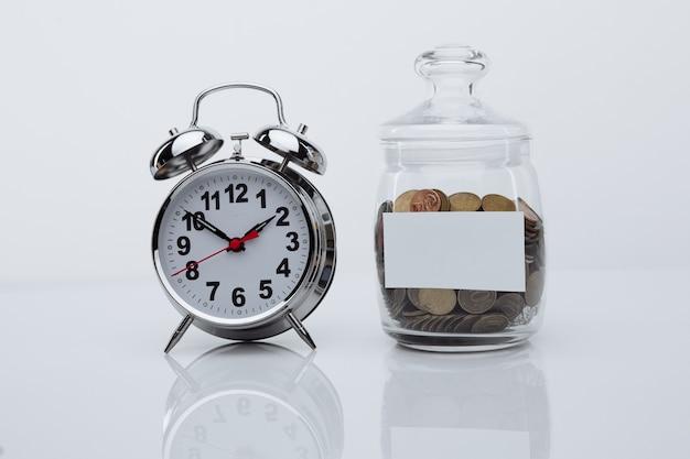 Monedas en un banco de cristal con espacio para texto y despertador en una habitación blanca. el tiempo es dinero