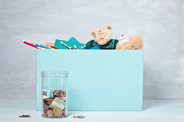 Monedas, billetes en frasco de dinero y caja con donaciones
