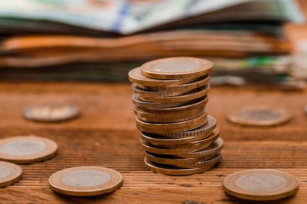 Monedas, billetes en la mesa de madera.