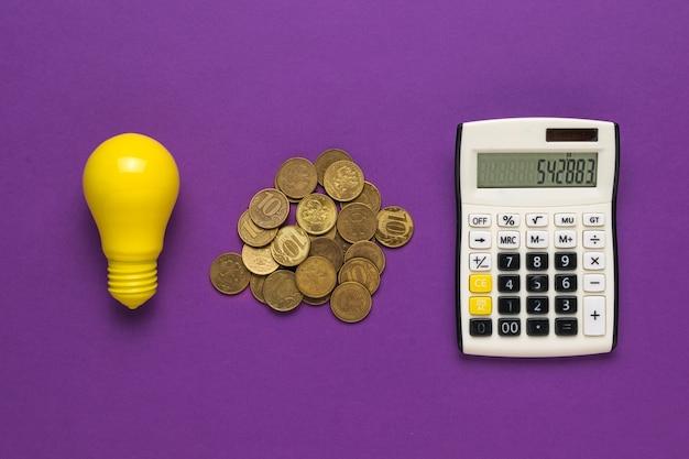 Monedas, una bombilla y una calculadora sobre un fondo morado. el concepto de incrementar los pagos por electricidad.