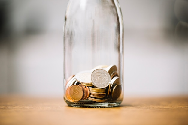 Monedas en la botella de vidrio en la superficie de madera