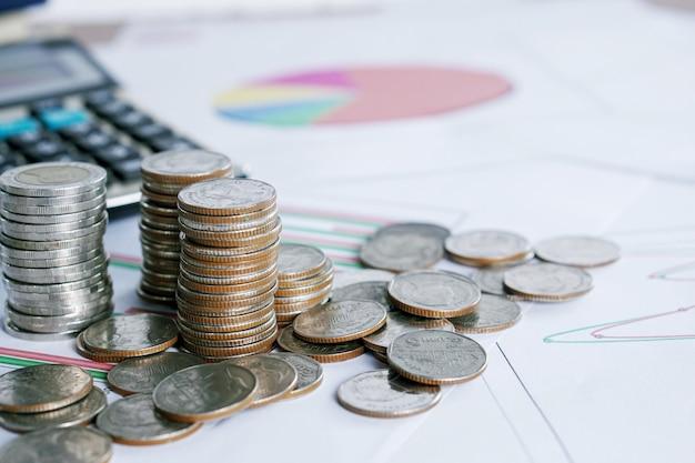 Monedas con calculadora en gráfico financiero