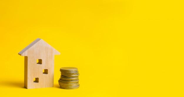Monedas y casa de madera sobre un fondo amarillo.