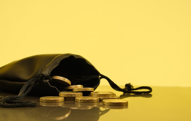 Monedas cayendo de una bolsa de dinero, fondo dorado.