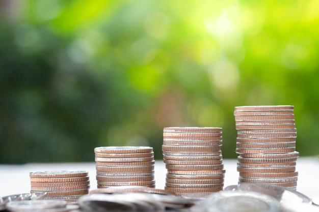 Monedas crecientes del primer que apilan con el fondo y la luz del sol del verdor.