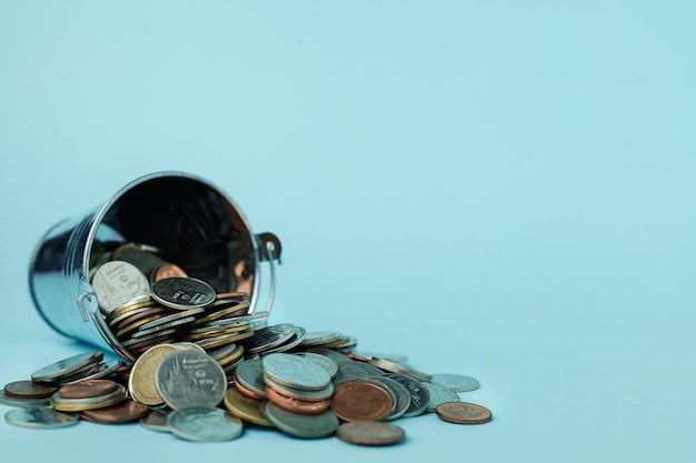 Monedas con un cubo de lata sobre fondo azul.