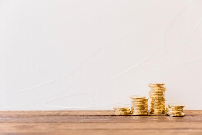 Monedas de oro apiladas delante de la pared