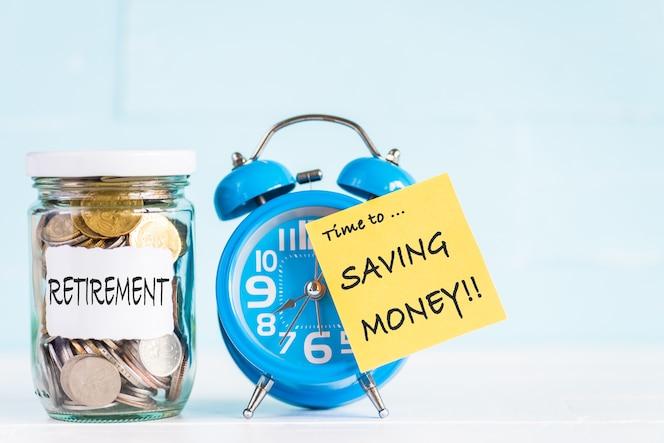 Monedas de tarro de cristal y despertador con tiempo para ahorrar dinero