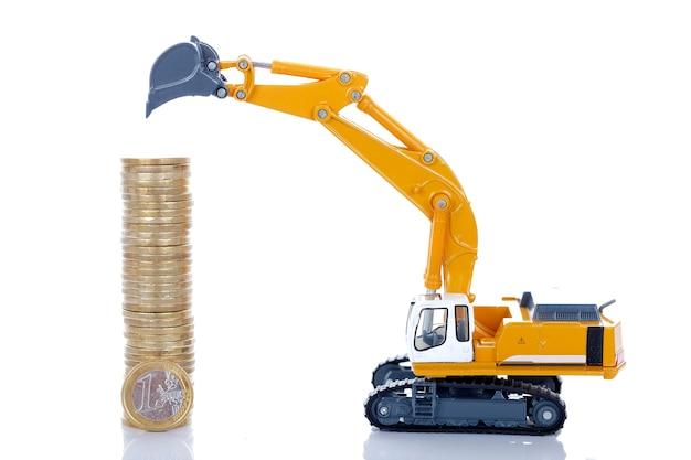Monedas de dinero en euros con excavadora aislado en espacio en blanco