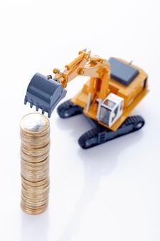 Monedas de dinero en euros con excavadora en blanco