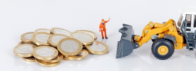 Monedas de dinero en euros con excavadora y trabajador en blanco