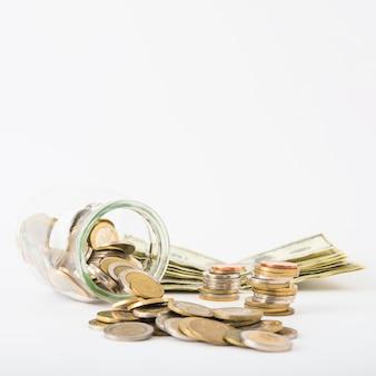 Monedas dispersas de jar con billetes en la mesa
