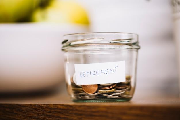Monedas en un recipiente de vidrio abierto retiro en la mesa