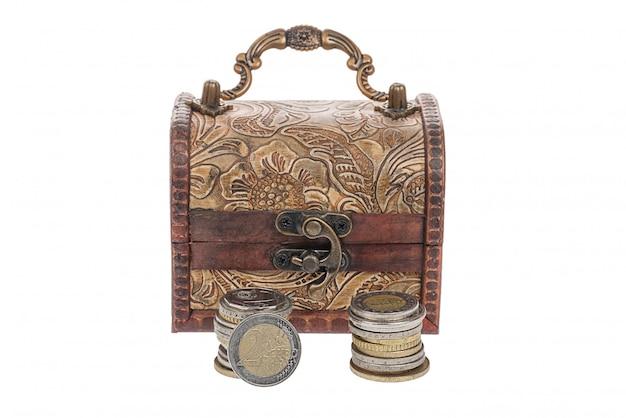 Monedas de euro cerca del viejo cofre retro vintage con aislado