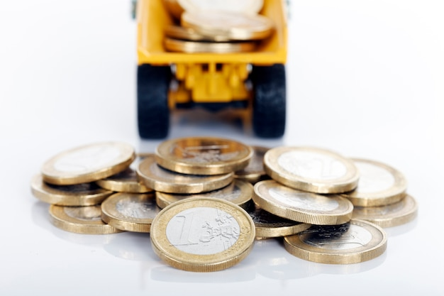 Monedas de euro dinero y camión en espacio en blanco