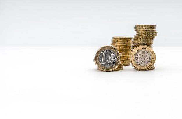 Monedas de un euro y una libra en primer plano con monedas amontonadas en el fondo.