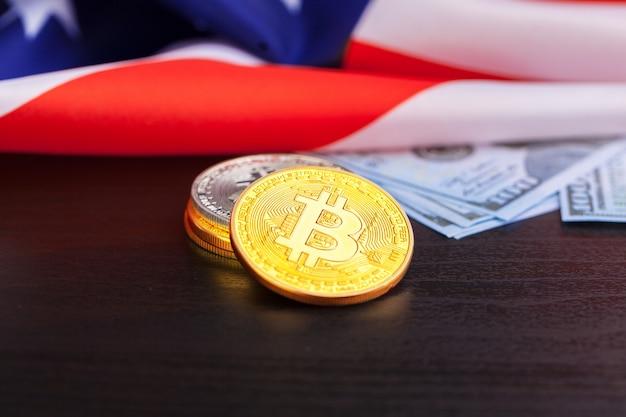 Monedas físicas de bitcoin en bandera estadounidense con dólares
