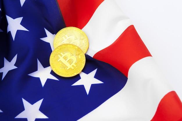 Monedas físicas de bitcoin en bandera estadounidense con monedas de bitcoin