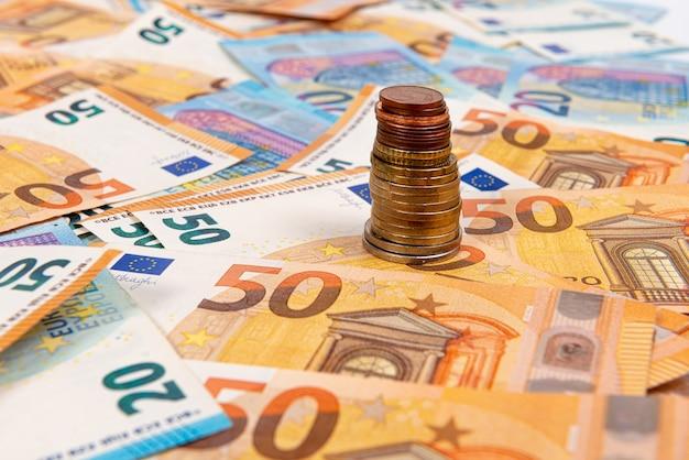Monedas en el fondo de los billetes en euros, el billete de euro como parte del sistema económico y comercial, primer plano