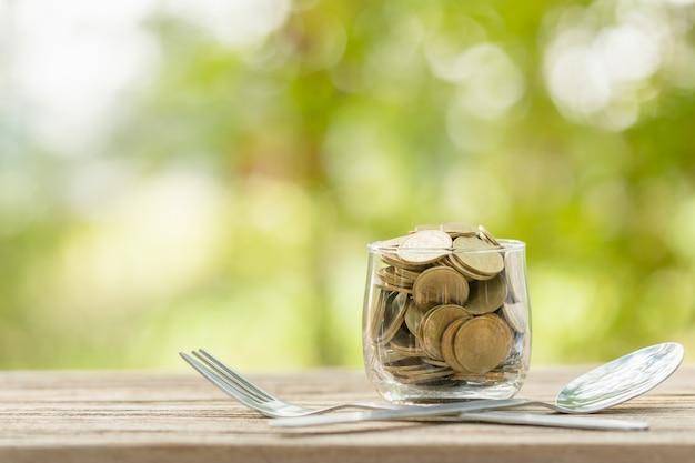 Monedas en frasco de dinero transparente, tenedor y cuchara en la mesa de madera con luz verde borrosa ahorro de dinero para comer concepto
