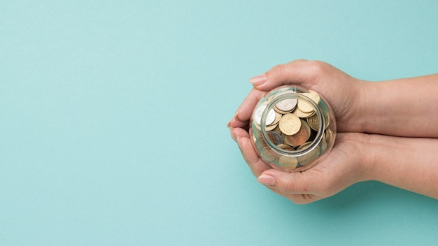 Monedas en frasco de vidrio con espacio de copia
