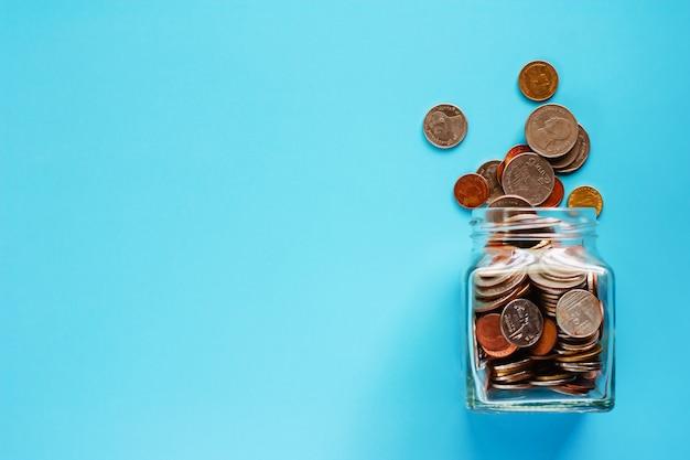 Monedas en frasco de vidrio y en el exterior, dinero en moneda tailandesa sobre fondo azul