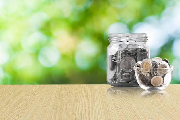Monedas en un frasco de vidrio sobre piso de madera, monedas de ahorro - concepto de inversión e interés concepto de ahorro de dinero, dinero en crecimiento en la hucha aislado sobre fondo verde