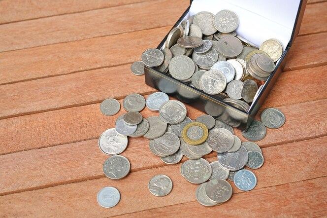 Monedas internacionales llenas en un cuadro cuadrado negro sobre fondo de tablón de madera