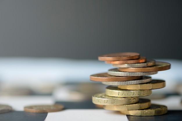 Monedas de libra esterlina apiladas en la mesa de ajedrez con fondo negro