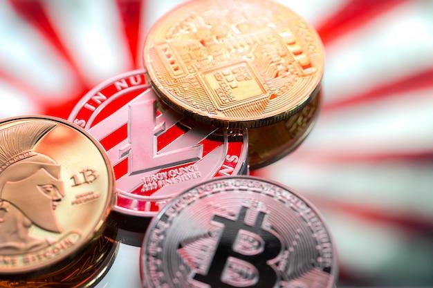 Monedas litecoin y bitcoin, en el contexto de japón y la bandera japonesa, el concepto de dinero virtual, primer plano.