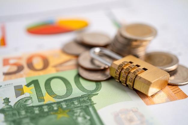 Monedas y llave de bloqueo de contraseña digital de seguridad dorada con billetes en euros
