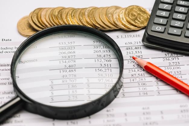 Monedas; lupa; lápiz y calculadora en informe financiero