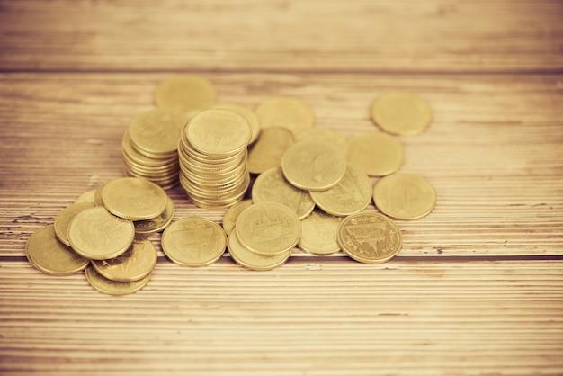Monedas en la mesa pila de monedas de oro en dinero de madera financiera