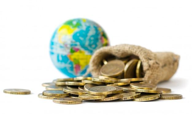 Monedas de metal vertidas de una bolsa y globo terráqueo