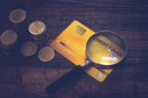 Monedas de negocios con tarjeta y lupa sobre mesa de madera, buró de crédito y aprobación de crédito financiero