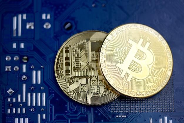 Monedas de oro de criptomonedas en placa de circuito de computadora