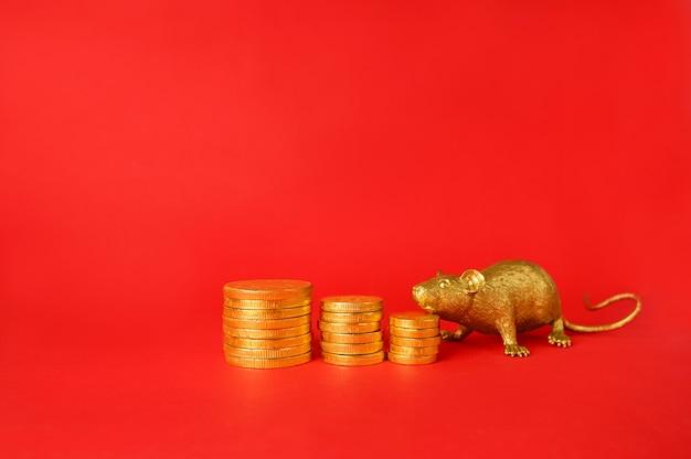 Monedas de oro y rata de oro sobre un fondo rojo, rata zodiaco chino.