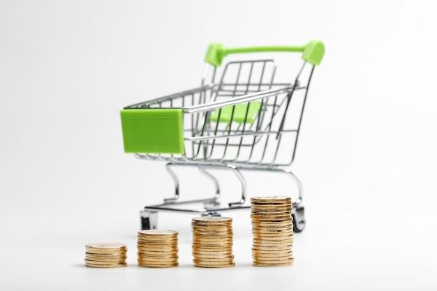 Monedas pila y carrito de la compra sobre un fondo blanco