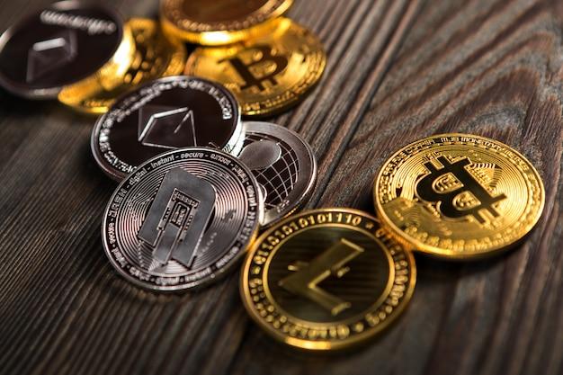 Monedas de plata y oro con bitcoin, rizo y símbolo etéreo.