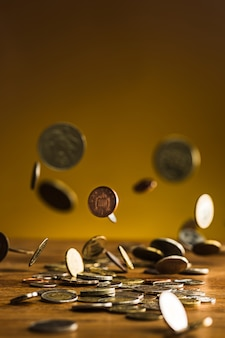 Las monedas de plata y oro y las monedas que caen en la pared de madera