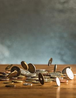 Las monedas de plata y oro y las monedas que caen sobre fondo de madera