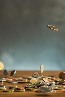 Las monedas de plata y oro y monedas que caen sobre fondo de madera