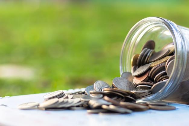 Monedas que se derraman de un dinero de vidrio tarro y dinero concepto monedas de ahorro.