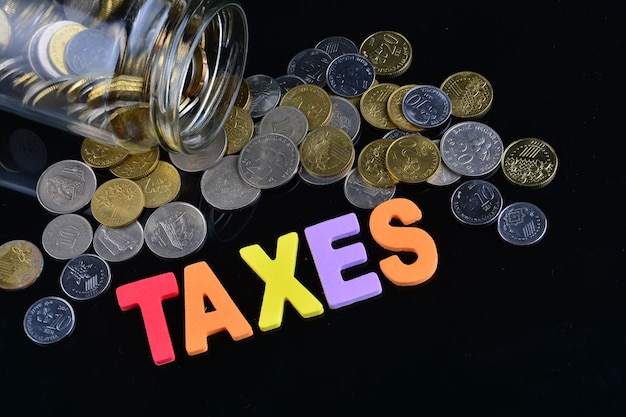 Monedas que se derraman de un tarro de dinero con la palabra impuestos