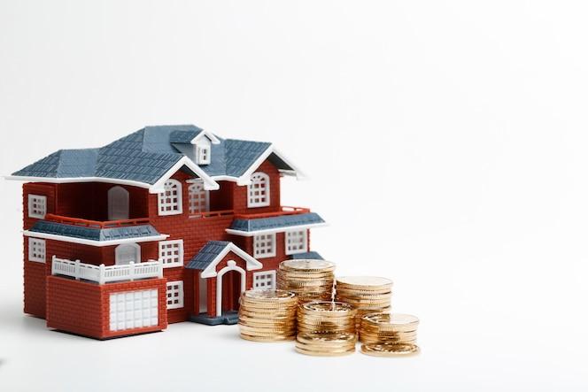 Monedas rmb apiladas en frente del modelo de vivienda (precios de la vivienda, compra de vivienda, bienes raíces, concepto de hipoteca)