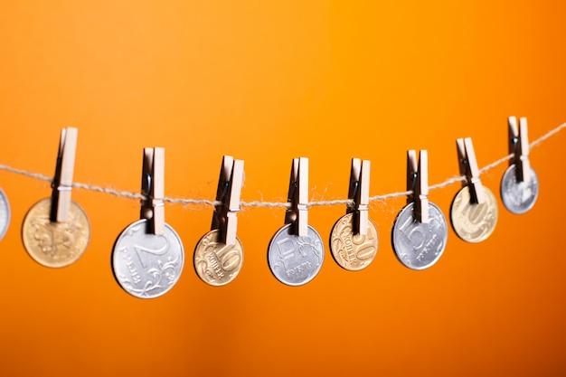 Monedas del rublo ruso colgando de pinzas de madera sobre un fondo naranja