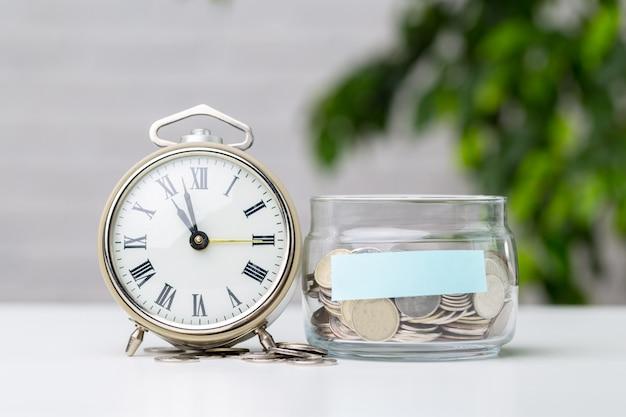 Monedas en tarro con despertador
